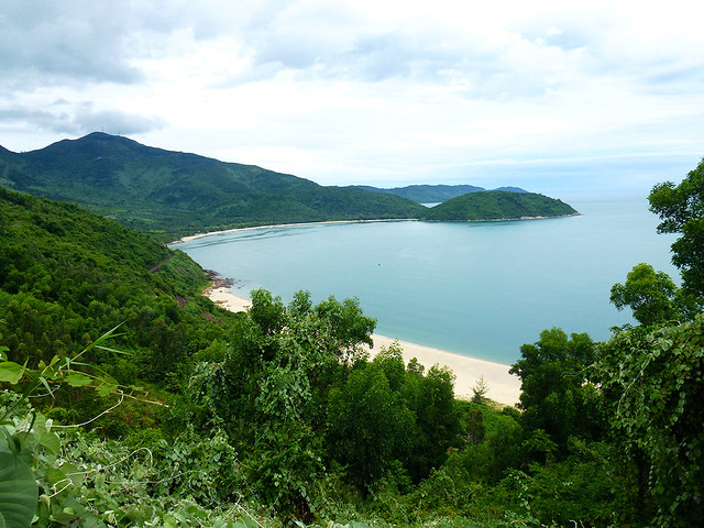 The sweep of an attractive bay along the Vietnamese coast just south of Hue, displaying its white sandy beach.