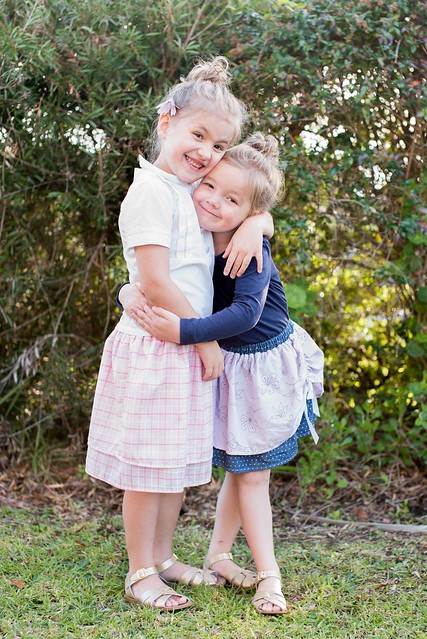Two girls stand in a garden, hugging.