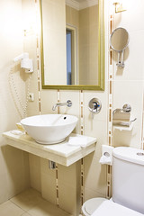 Bathroom, sink, toilet in light yellow tones