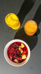 Two glasses of orange juice and a fruit salad with cherry, sour cherry, apple and water melon