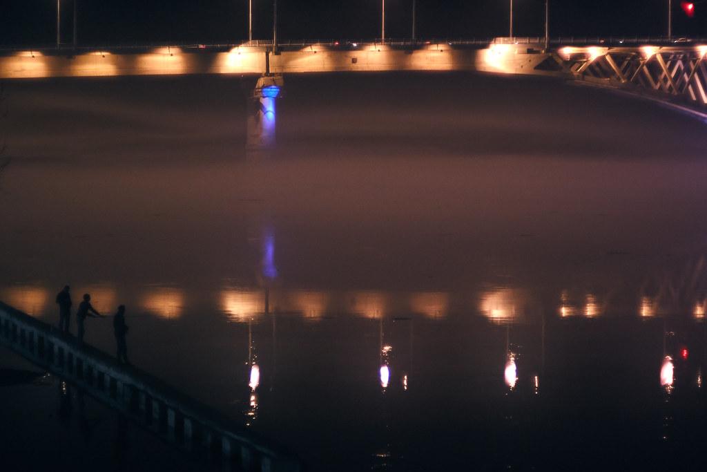 Nigh fishermen in the fog under the bridge
