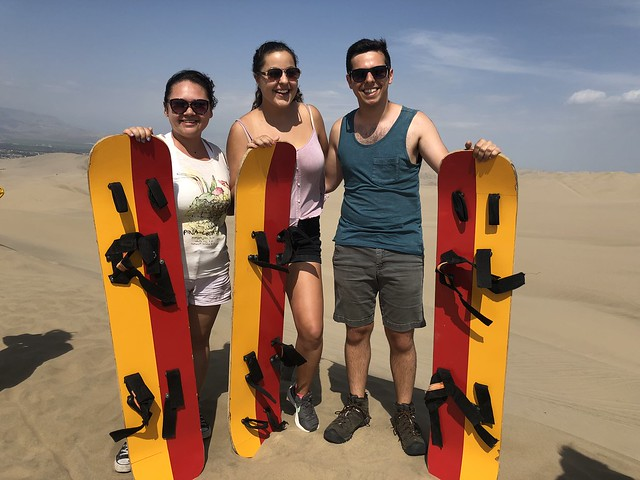 Three students standing with snad boards at the base of sand dunes.
