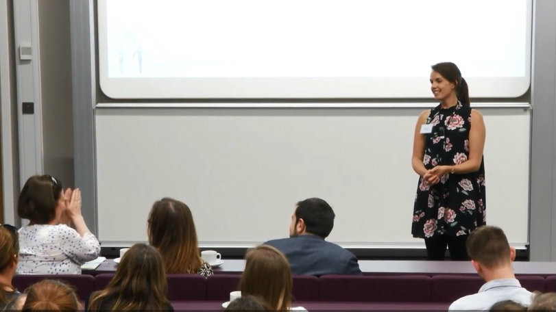 A PhD student talking to students in a lecture theatre