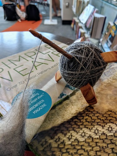 Spinning dyed Masham wool on Jenkins Lark spindle by irieknit and library book