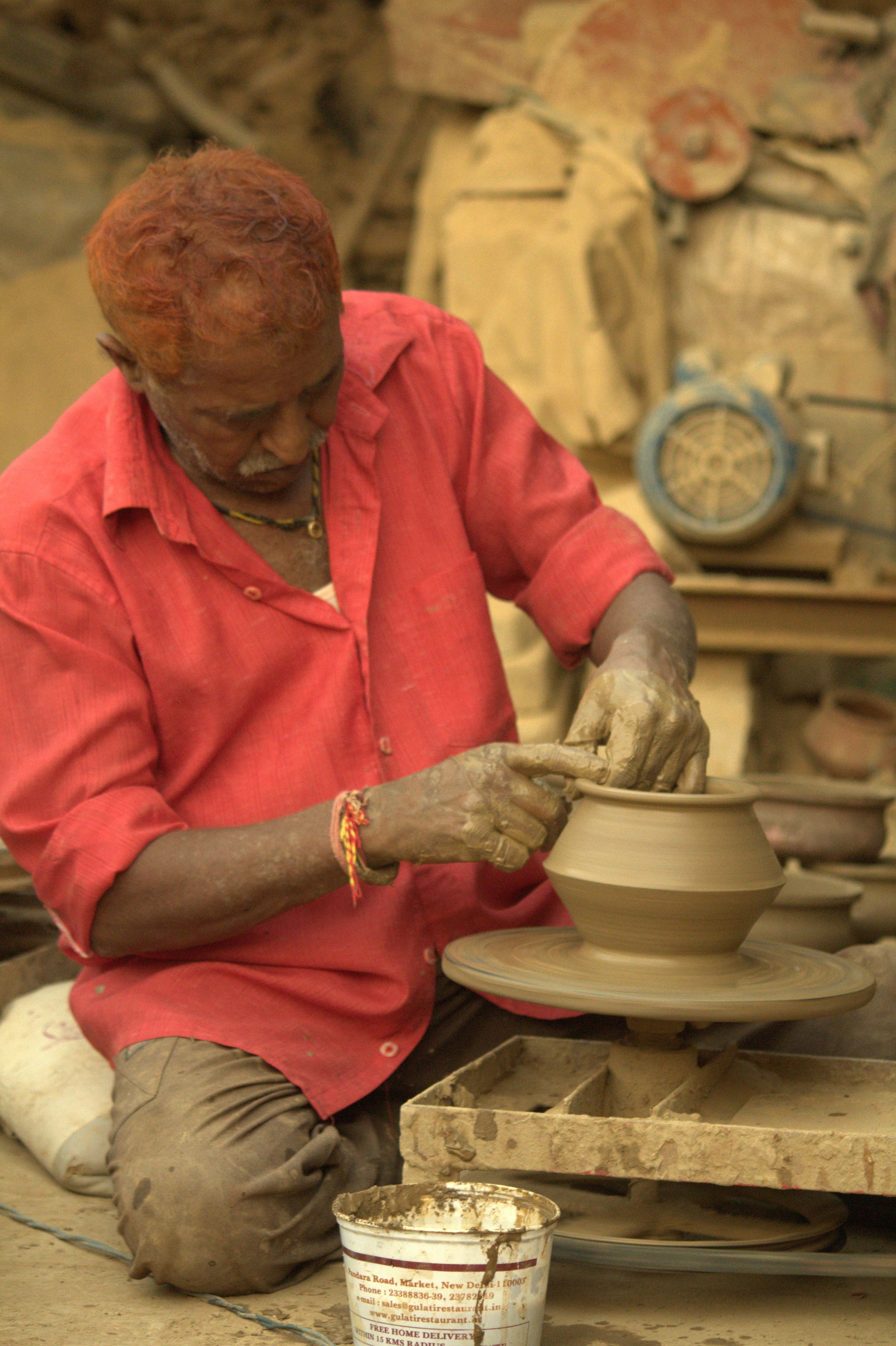 Mr. Kajor Ram making a Biryani pot on a spinning wheel with the traditional way of making clay pots in Punjab, India. Photo taken on January 1, 2007.