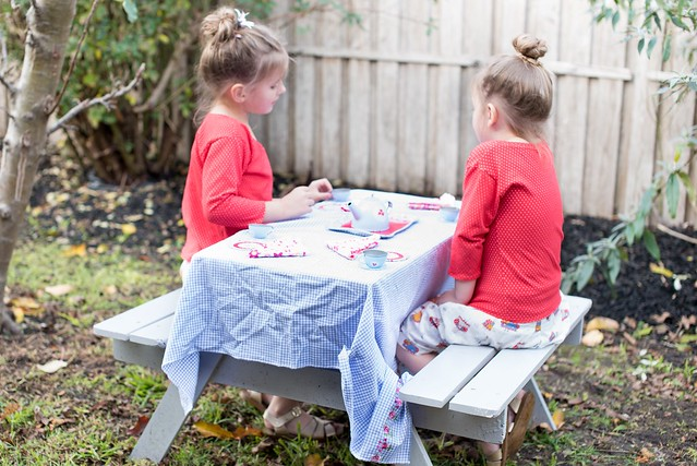 Two girls sit outside at a picnic table.