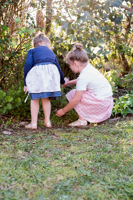 Two girls forage through greenery in a garden.