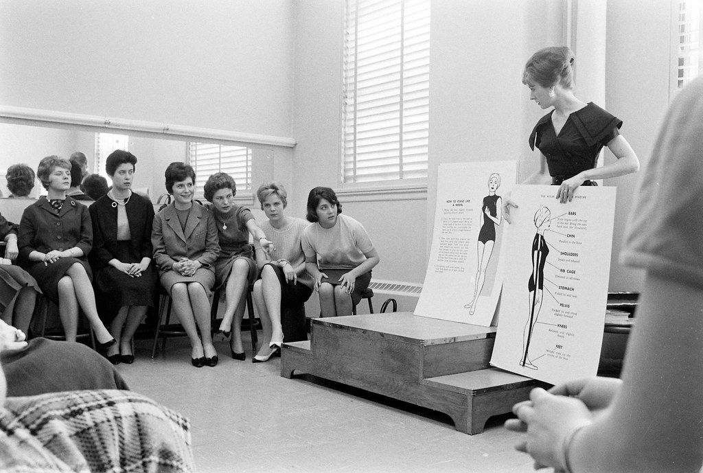 A group of young French and German women discussing posture during a session of Trans World Airlines stewardess school in Kansas City, Missouri, 1961.