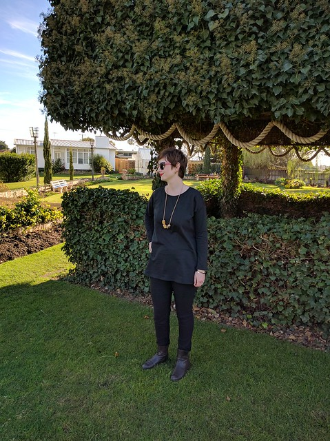 A woman standing in a garden, wearing a black french terry knit tee and black skinny pants.