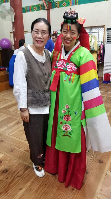 Student standing with instructor while wearing a colorful green and red traditional dress.