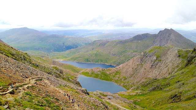 View from up Mount Snowdon overlooking two lakes and hills.