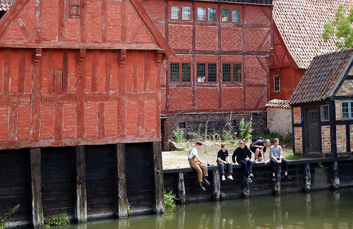 Boys hanging out on the canal surrounded by old half-timbered buildings in Den Gamle By, recreated villages set in different times, in Aarhus, Denmark