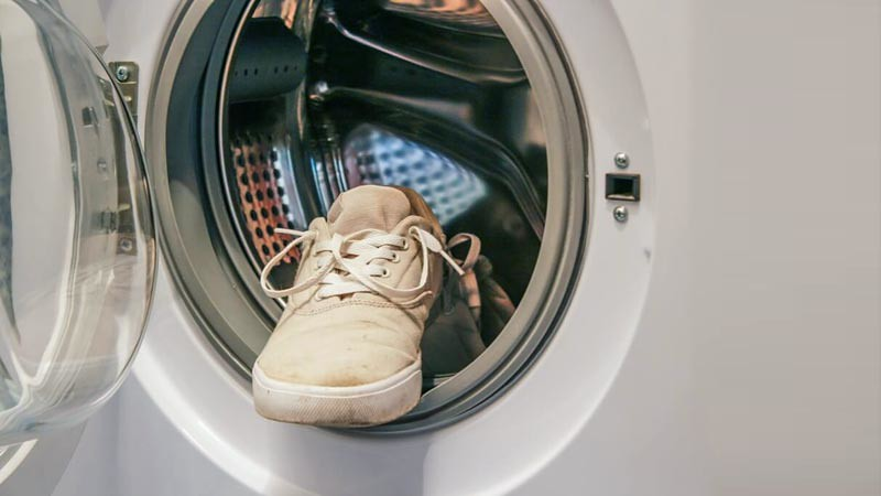 Membersihkan sepatu dengan mesin cuci.