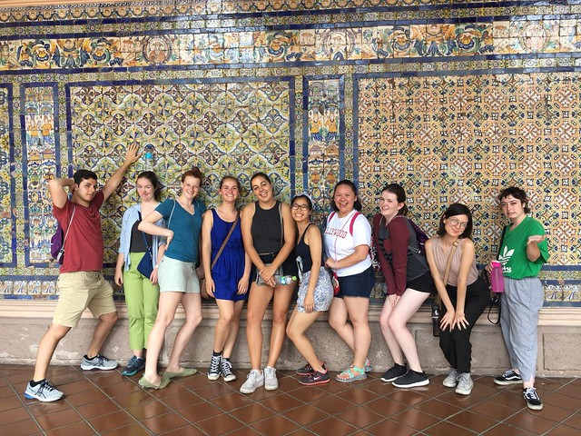 Students standing in front of large colorful wall of tile in a church in Peru.