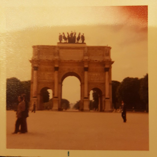 The Arc du Carrousel in Paris. There are a few people walking around in the foreground