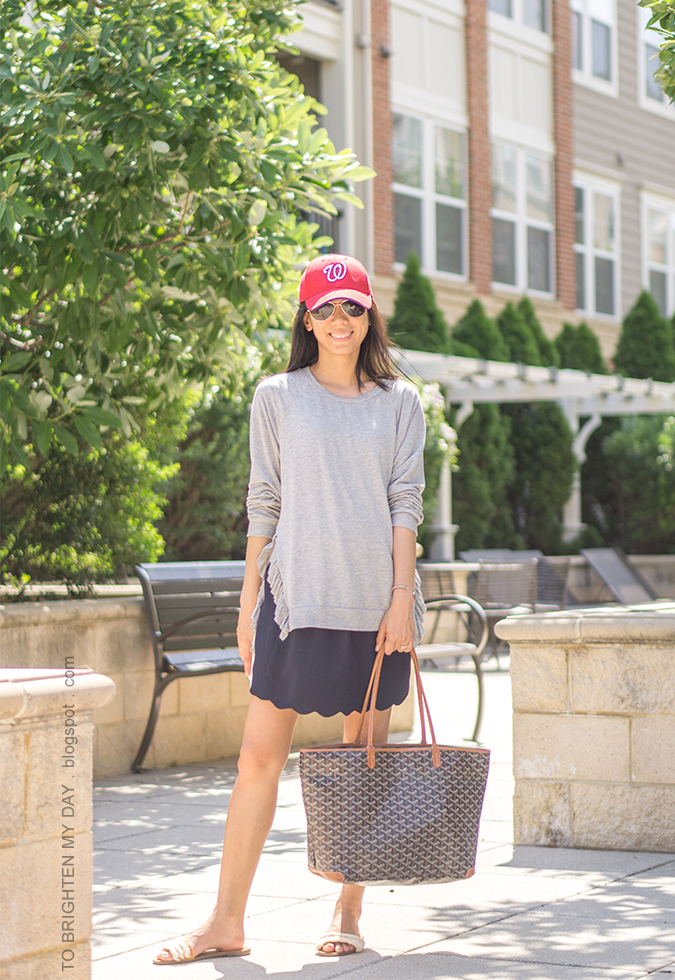 red baseball cap, gray tunic with side ruffle, silver cuff, patterned tote, navy scallop skirt, white flats with fringe