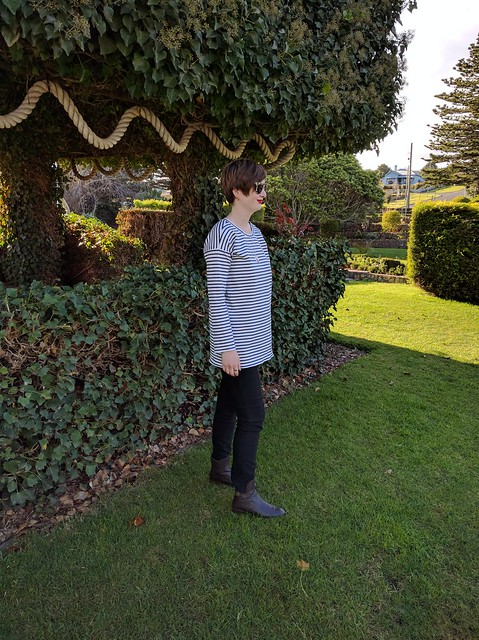 A woman standing in a garden, wearing a striped knit tee and black skinny pants.