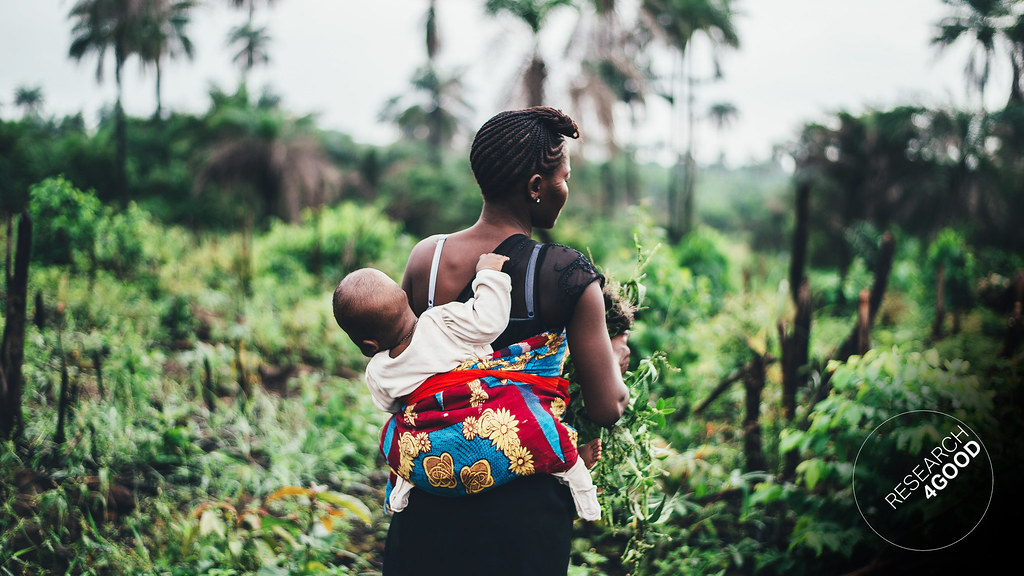 A woman with a baby on her back, picking plants in a jungle