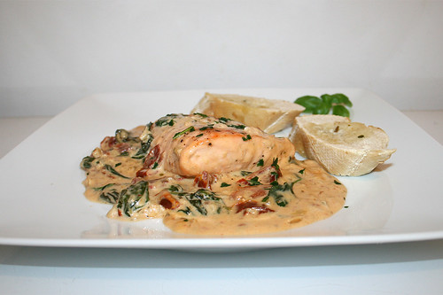 53 - Salmon filet in creamy sauce with dried tomatoes, spinach & garlic - Side view / Lachsfilet in cremiger Spinat-Knoblauch-Sauce mit getrockneten Tomaten - Seitenansicht