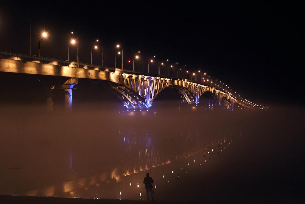 Night fisherman under the bridge in the fog