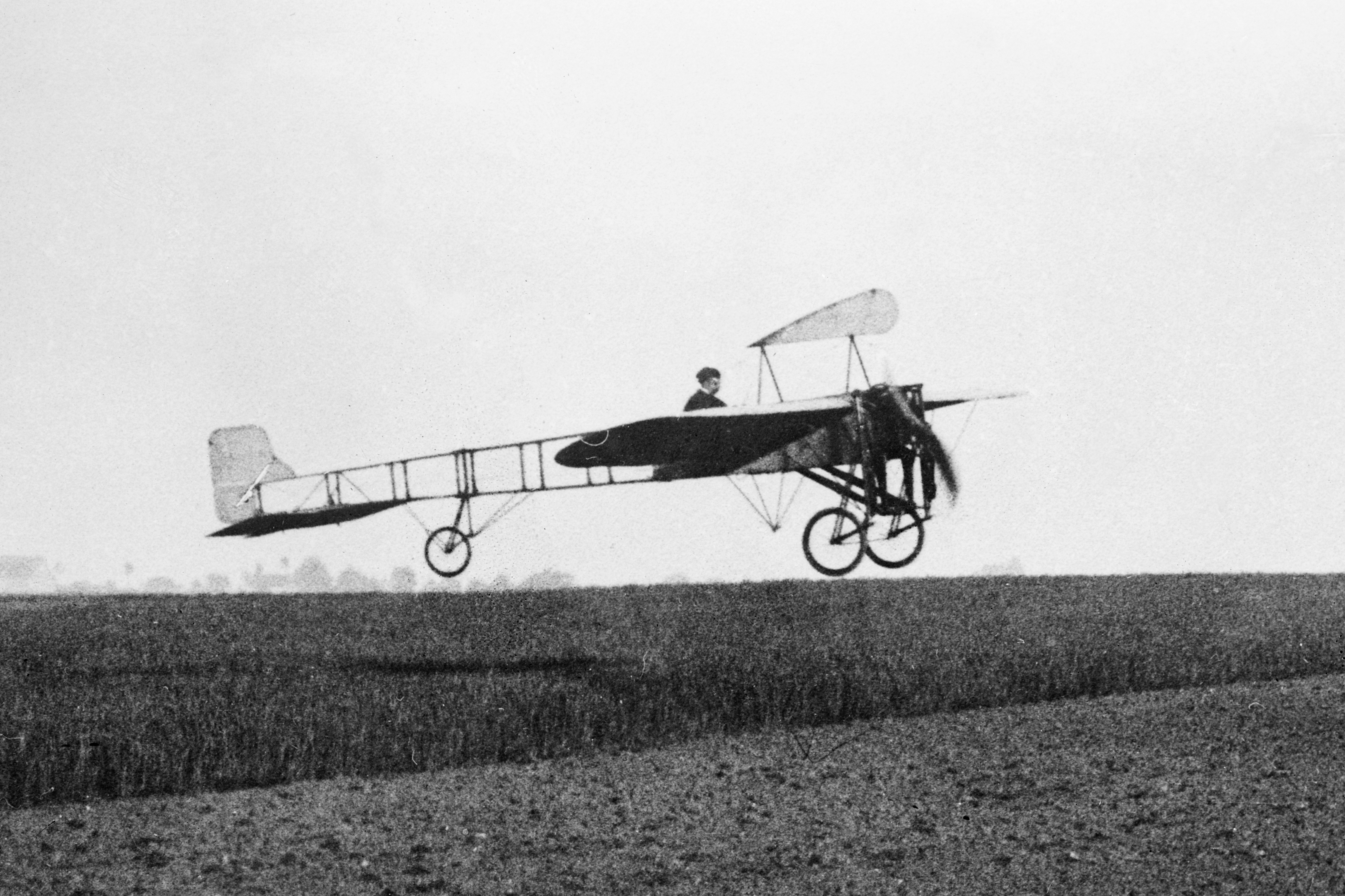 Louis Blériot in flight over a field in his Type XI aircraft. Photo taken in May 1909.