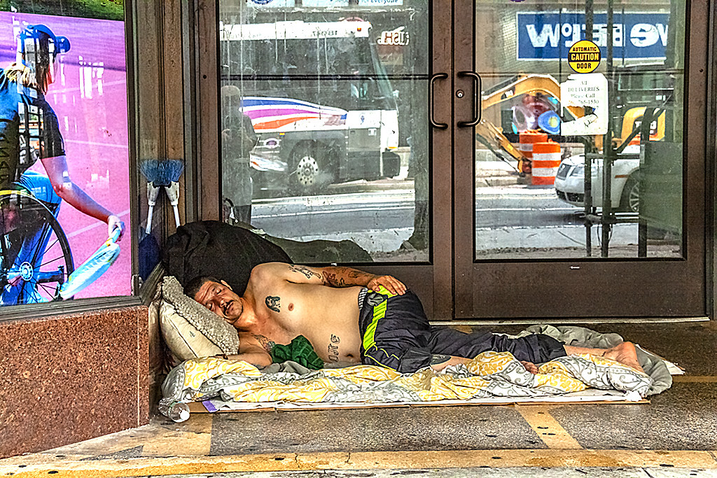 Shirtless man sleeping on sidewalk at 7th and Market--Center City