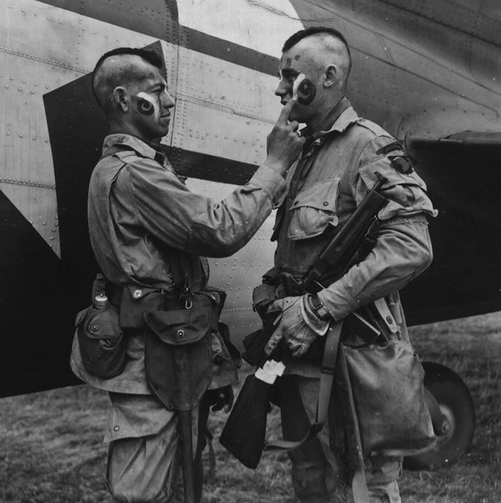 Filthy Thirteen member Clarence Ware applies war paint to Charles Plaudo, 5 June 1944. The idea was McNiece's, to honor his Native American heritage and to energize the men for the danger ahead.