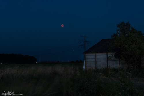 Rising blood moon eclipse over over a dilapidated barn