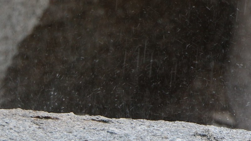 Zoomed-in view of raindrops splattering on granite as I waited for the rain to stop