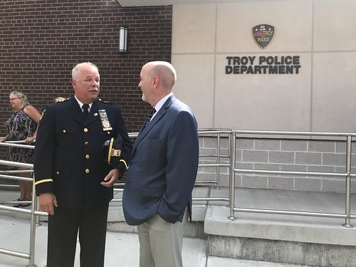 Captain Rick Sprague speaking with Mayor Patrick Madden in front of Troy Police Department headquarters. The Troy Police Department logo is visible on the concrete wall behind Captain Sprague and Mayor Madden