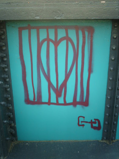 graffiti - red paint on blue background -- of a heart in a cage