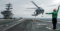 WATERS SOUTH OF JAPAN (Aug. 7, 2018) Aviation Ordnanceman Airman Myles Collins, from Houma, Louisiana, directs an MH-60S Sea Hawk, assigned to Helicopter Sea Combat Squadron (HSC) 12, to land on the flight deck of the Navy's forward-deployed aircraft carrier, USS Ronald Reagan (CVN 76). Ronald Reagan, the flagship of Carrier Strike Group 5, provides a combat-ready force that protects and defends the collective maritime interests of its allies and partners in the Indo-Pacific region. (U.S. Navy photo by Mass Communication Specialist 2nd Class Kenneth Abbate)