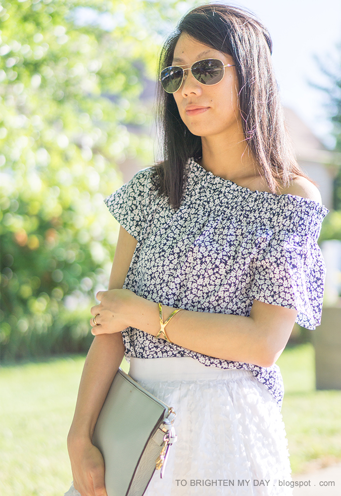 one shoulder floral top, gold jewelry, blue gray clutch, white clip dot midi skirt