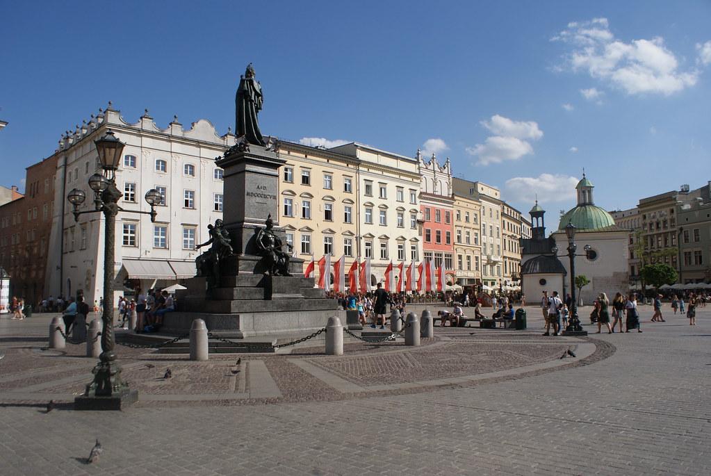Derrière la statue du poète Adam Mickiewicz sur la place du marché : le Rynek de Cracovie.