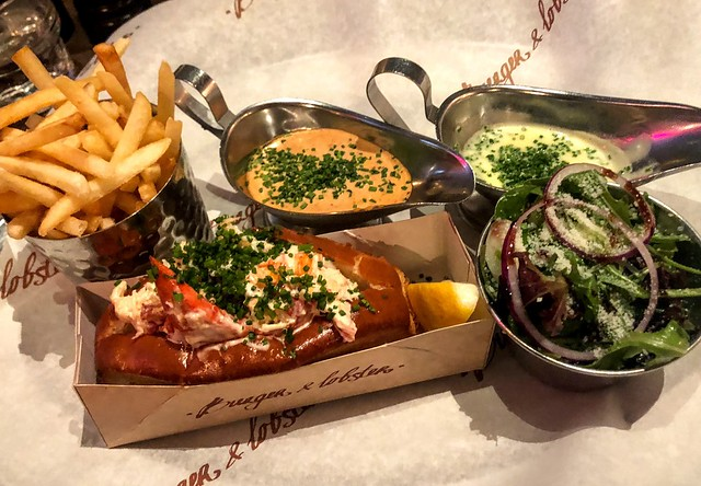 A lobster role next to a cup of fries, small salad, and two different sauces in gravy boats.
