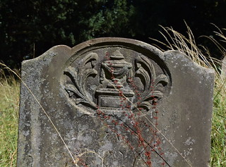 draped urn on a tomb flanked by fronds