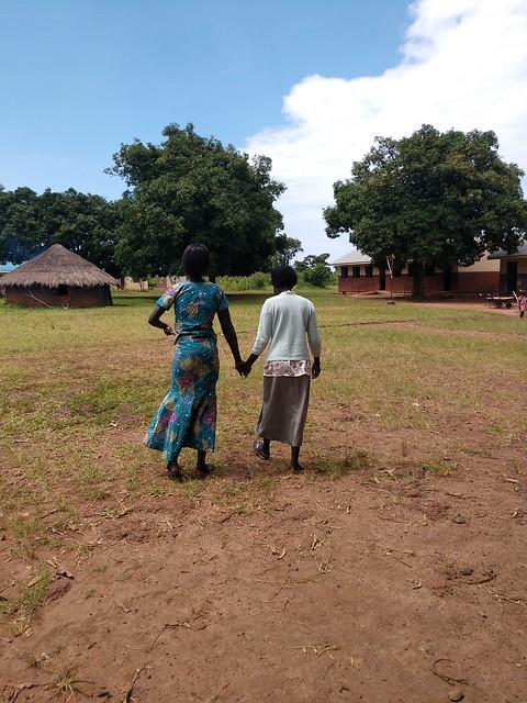 Nancy Okot walking with her former teacher