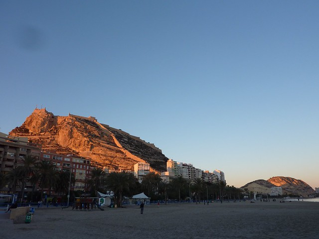 Bottom of mountain in Alicante that meets a beach at sunset.