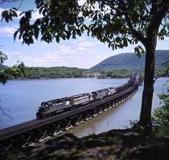 Penn Central SD35 6028, EL SD45 3613, a PC GP, and EL SDP45 3655 north bound coal train (Roseton) on Iona trestle in Bear Mountain NY; summer 1976. The firman takes a brake out of the cab