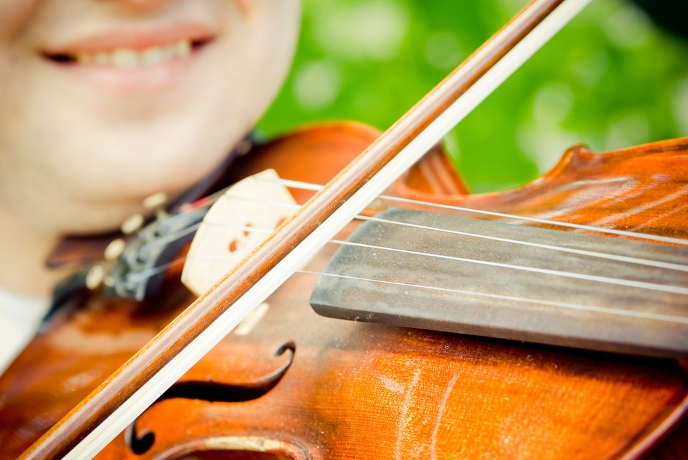 Close-up photo of violinist playfully smiling while practicing