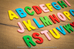 Colorful wooden alphabet letters isolated on wooden background