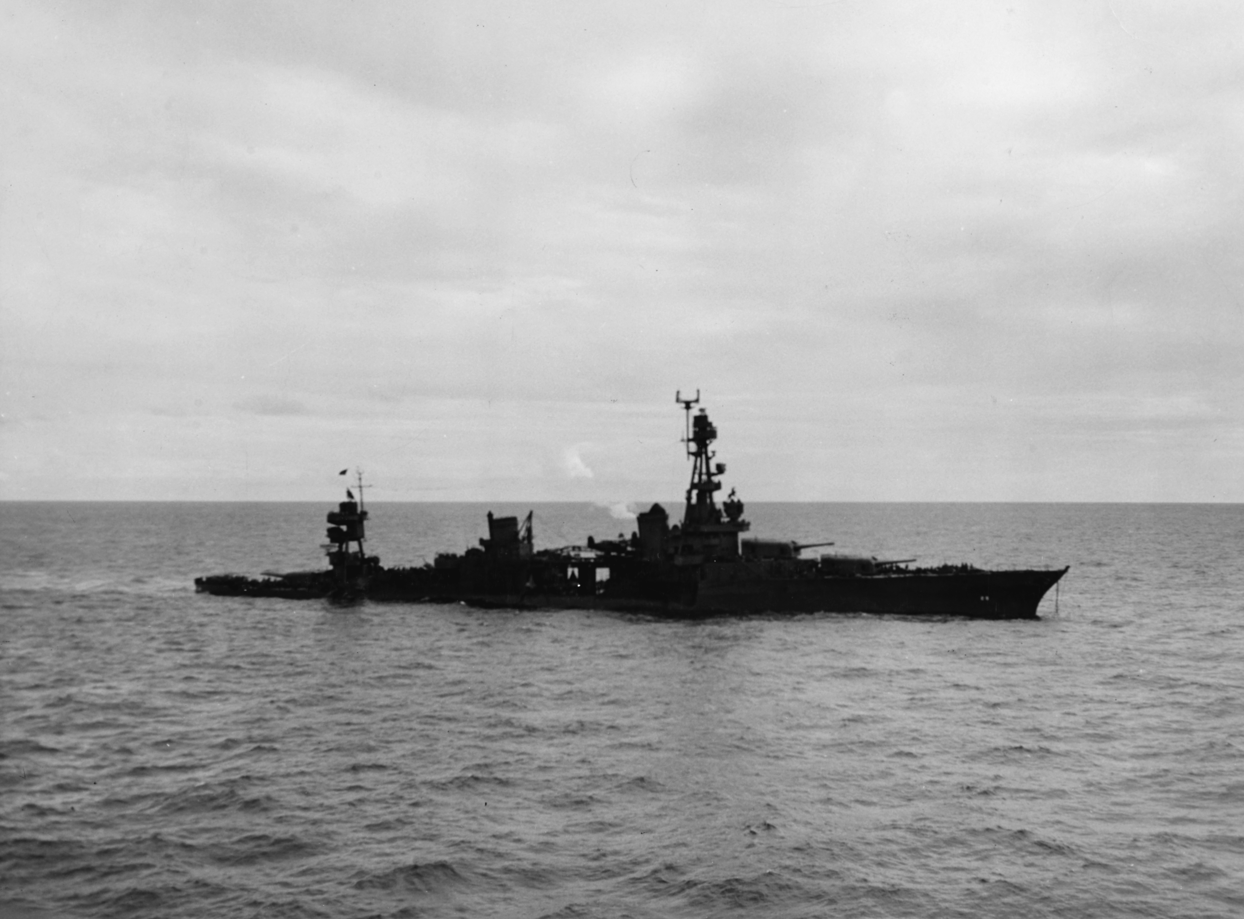The U.S. Navy heavy cruiser USS Chicago (CA-29) low in the water on January 30, 1943, after she had been torpedoed by Japanese aircraft during the Battle of Rennell Island. U.S. Navy photo NH 55141
