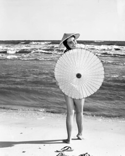 Pat Finn posing on the St. Andrews State Park beach with an umbrella - Florida