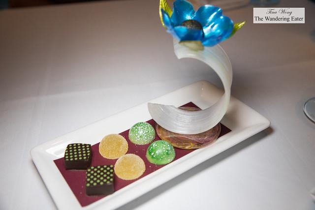 Mignardes - Pulled sugar sculpture with blue flower, duo of chocolates and a lemon pâté de fruit