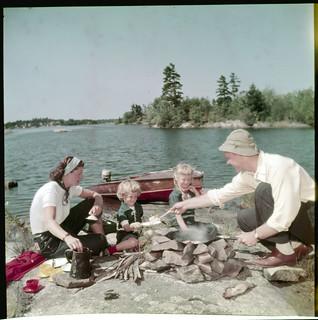 Family making a shore dinner on Stony Lake. Mother, Father, and two little girls around fire in the foreground, Ontario / Famille préparant le souper sur la rive du lac Stony. Au premier plan, on voit la mère, le père et deux petites filles autour d'