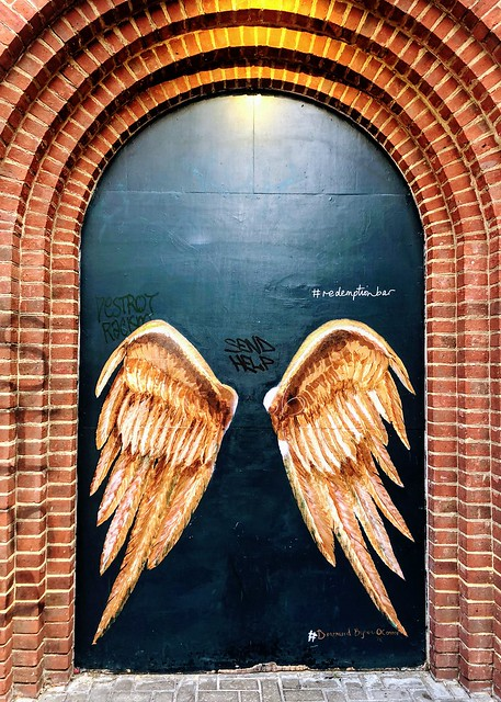Small arched door surrounded by arch of bricks. Two large golden wings are painted on the door.