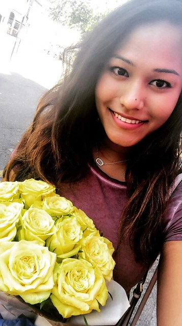 Student in maroon shirt holding bouquet of yellow roses.