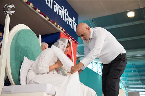 Puts the white scarf (Dupatta), around Rev. Sudiksha Ji's neck through a devotee.