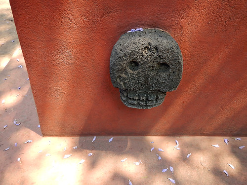 Lava skull on the dark red wall of the pyramid in the garden of the artist Frida Kahlo's 'Casa Azul', the cobalt blue house in Coyoacán, Mexico