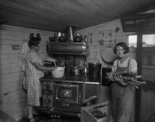 Two women preparing dinner in their first home, St. Jean Baptiste, Manitoba / Deux femmes préparant le souper dans leur première maison, Saint-Jean-Baptiste (Manitoba)